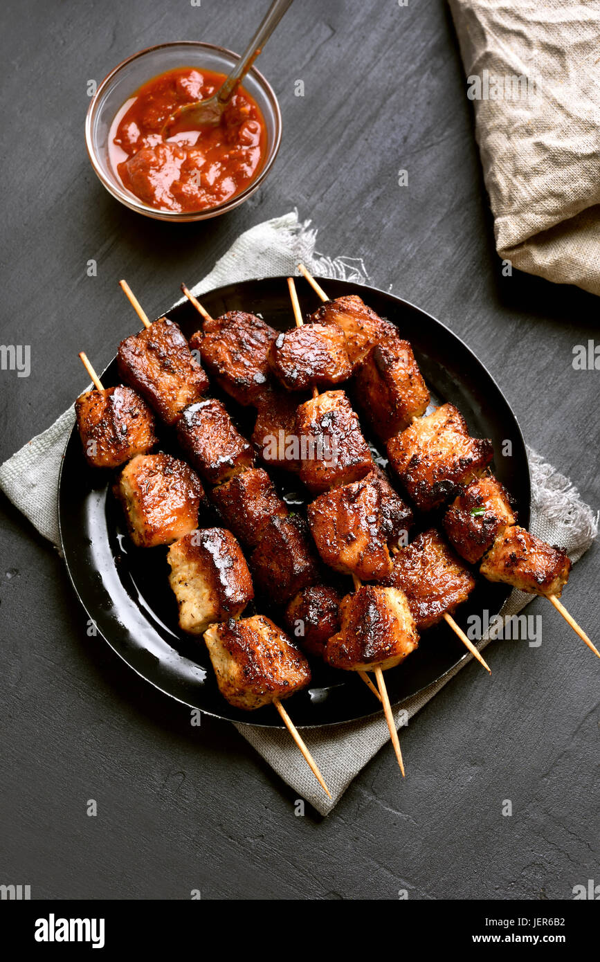 Homemade grilled pork skewers on black background, top view - Stock Image