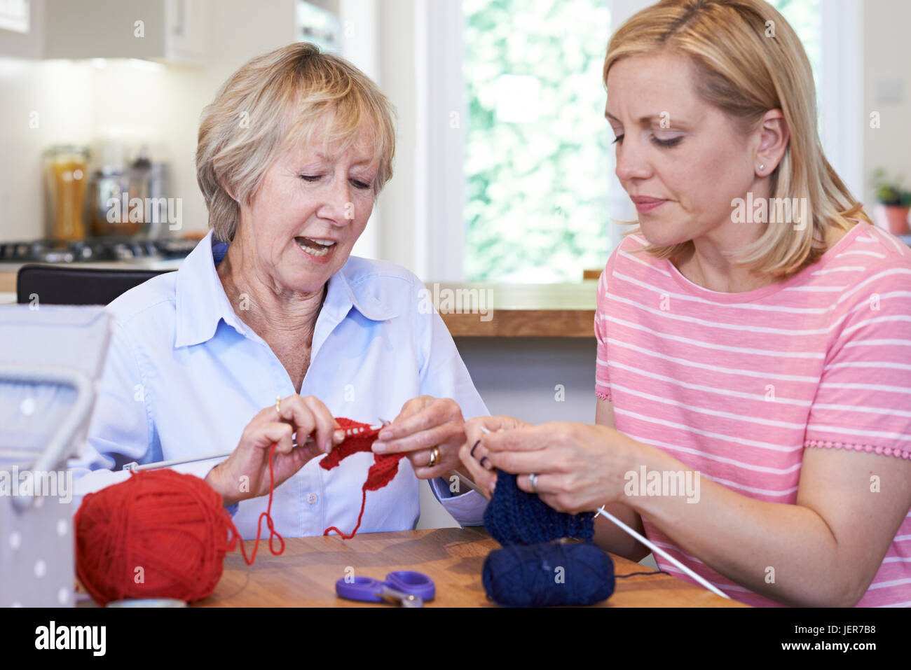 Senior And Mature Female Friends Knitting At Home Together - Stock Image