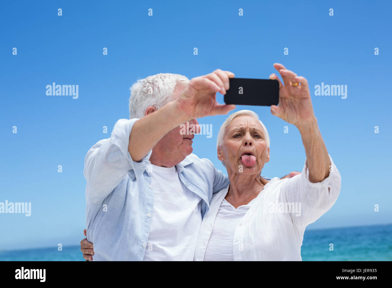 Senior couple taking a selfie and grimacing - Stock Image