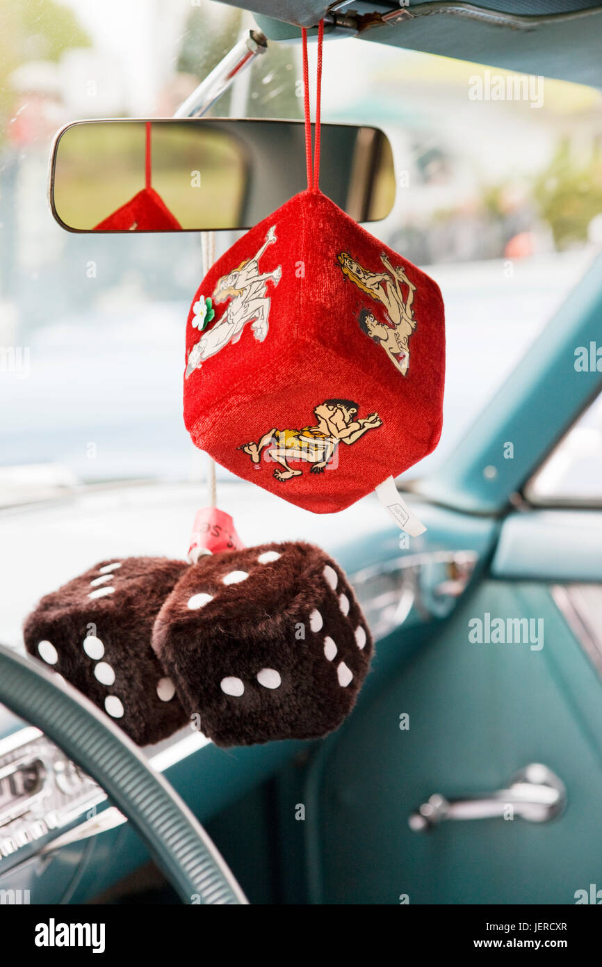 Fluffy dice hanging from rear-view mirror in car - Stock Image