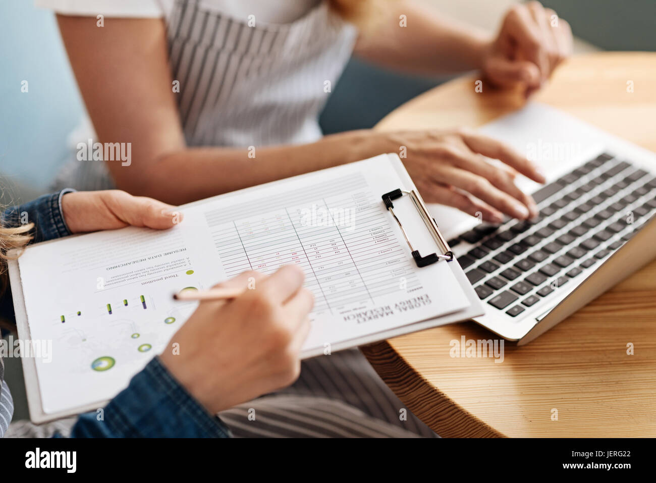 Dainty female hands holding a printout in sheet holder - Stock Image