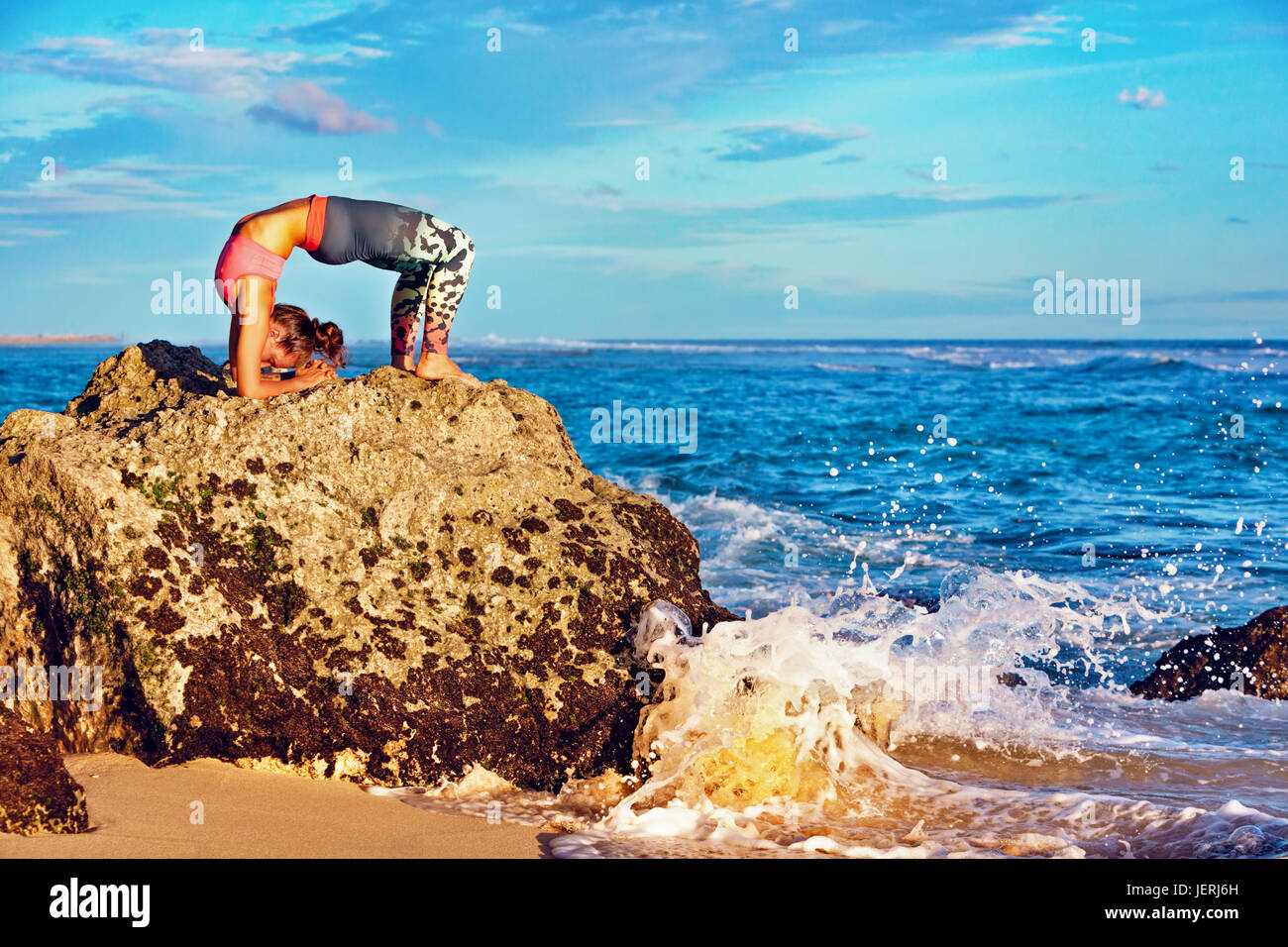 Meditation on sea surf with splashes background. Active woman on beach rock in yoga pose to keep fit and health. - Stock Image