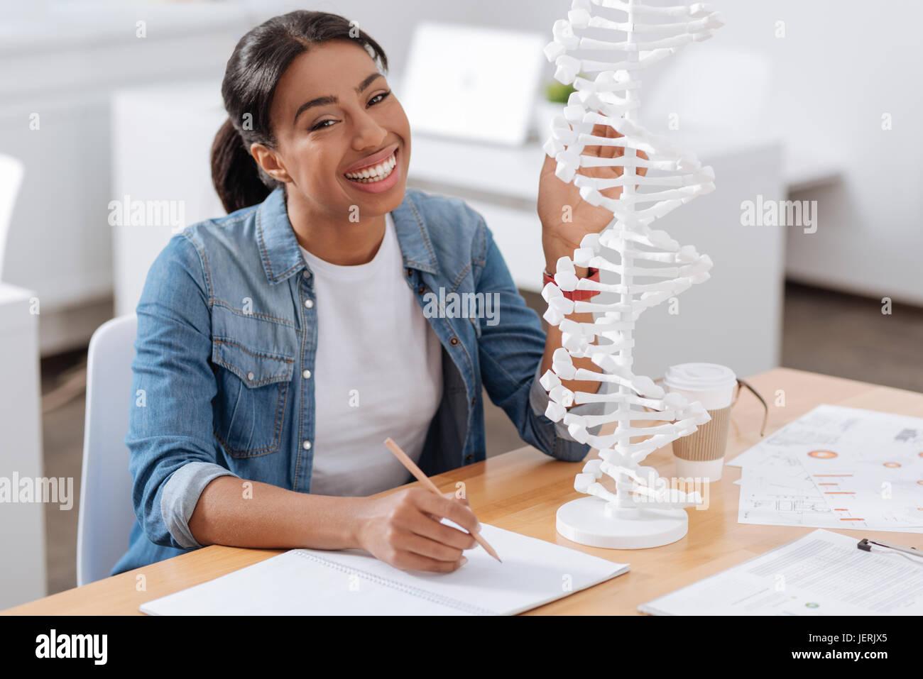 Happy nice student studying genetics - Stock Image