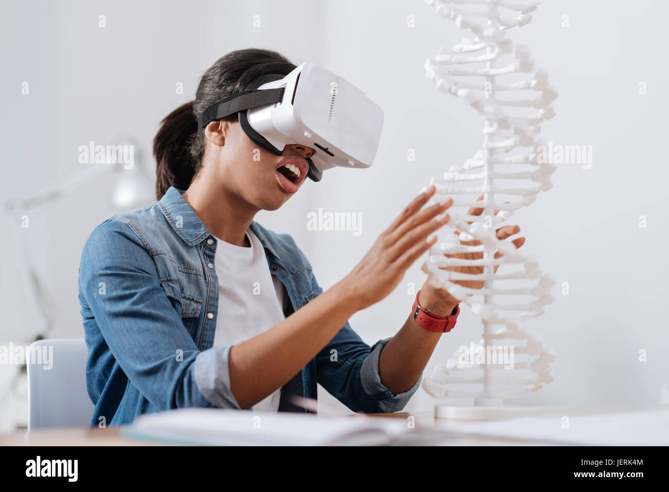 Nice pleasant woman studying microbiology - Stock Image