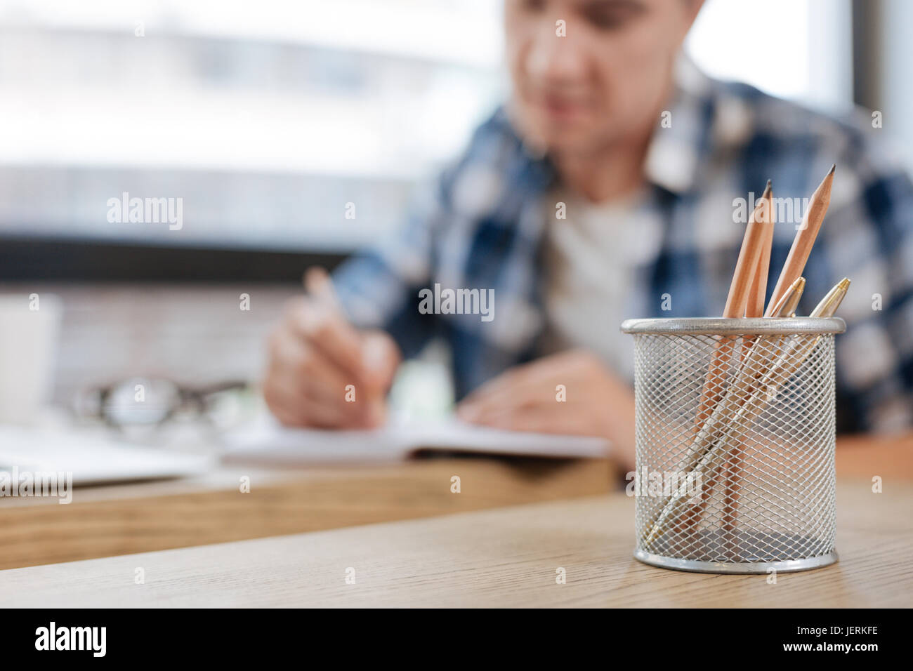 Persistent analytical man writing his schedule - Stock Image