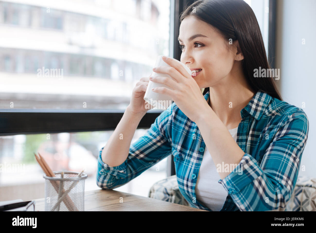 Dreamy inspired girl looking out of the window - Stock Image