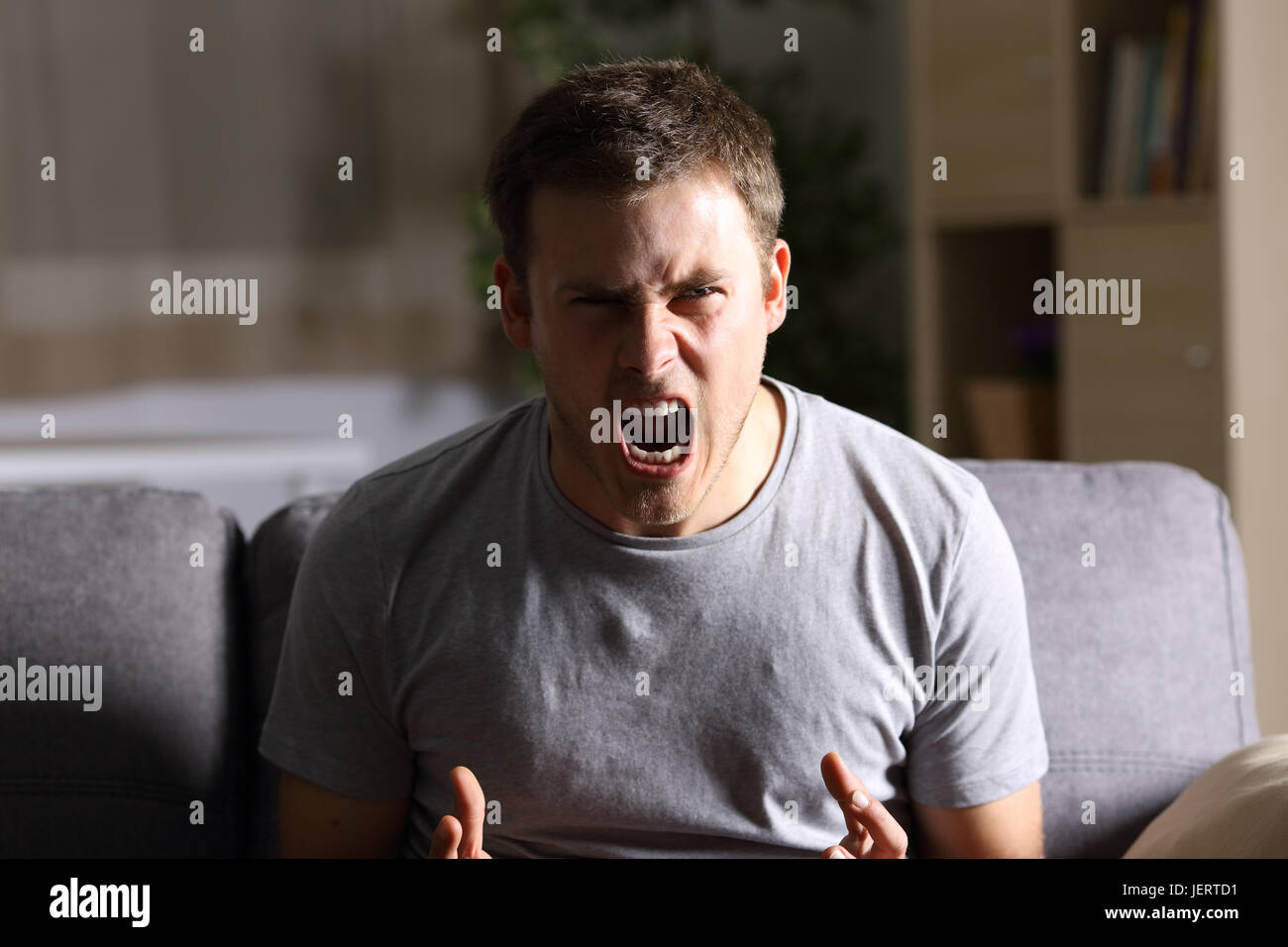 Casual furious man shouting and looking at you sitting on a sofa at home with a dark light in the background Stock Photo