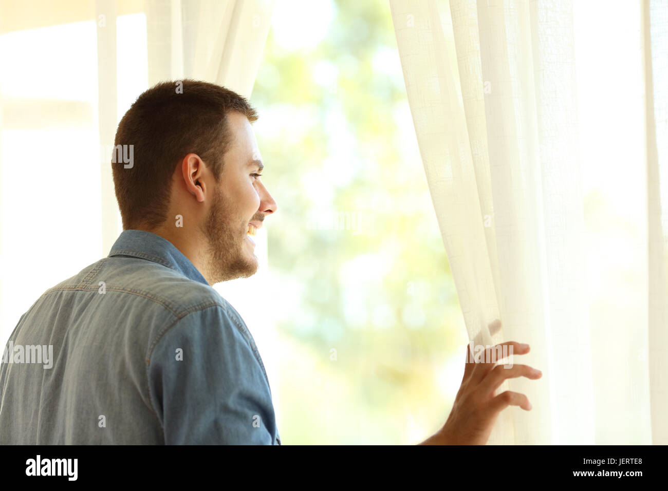 Single pensive man looking outdoors through a window at home or hotel - Stock Image