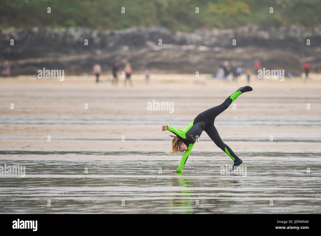 A young girl wearing a wetsuit doing a cartwheel on Fistral Beach in Newquay, Cornwall. - Stock Image