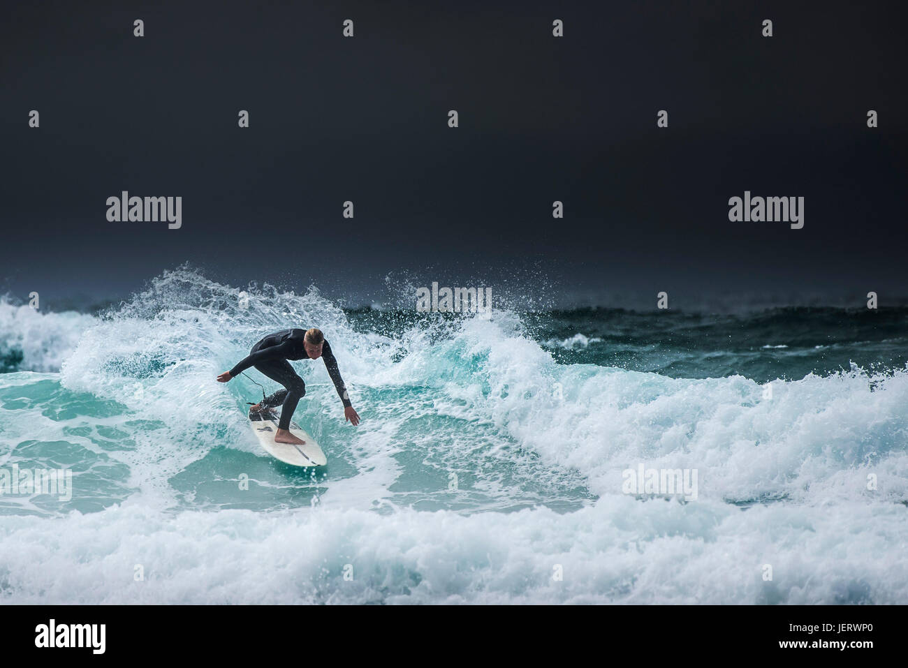 Surfing UK.  A lone surfer riding a wave as dark clouds gather over the North Cornwall coast. - Stock Image