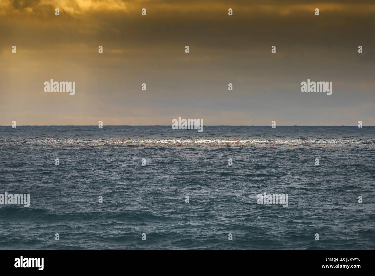 Sunight breaking though clouds to illuminate the sea. - Stock Image
