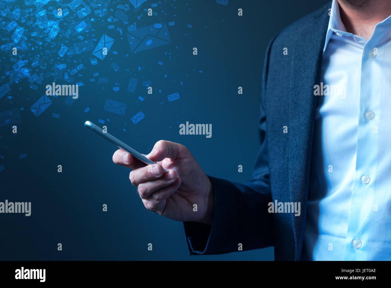 Businessman sending bulk messages using smartphone, male business person in elegant suit delivering e-mails, newsletters - Stock Image