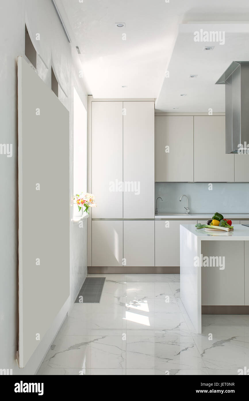 Modern kitchen with white walls and light tiled floor. There are ...