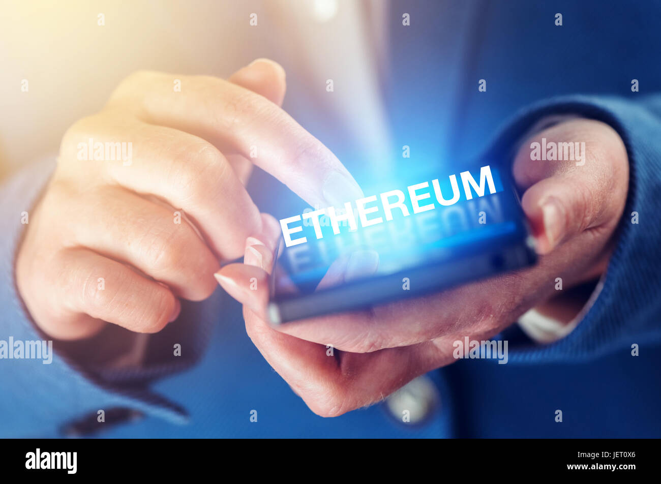 Ethereum cryptocurrency concept with female hands and smartphone - Stock Image