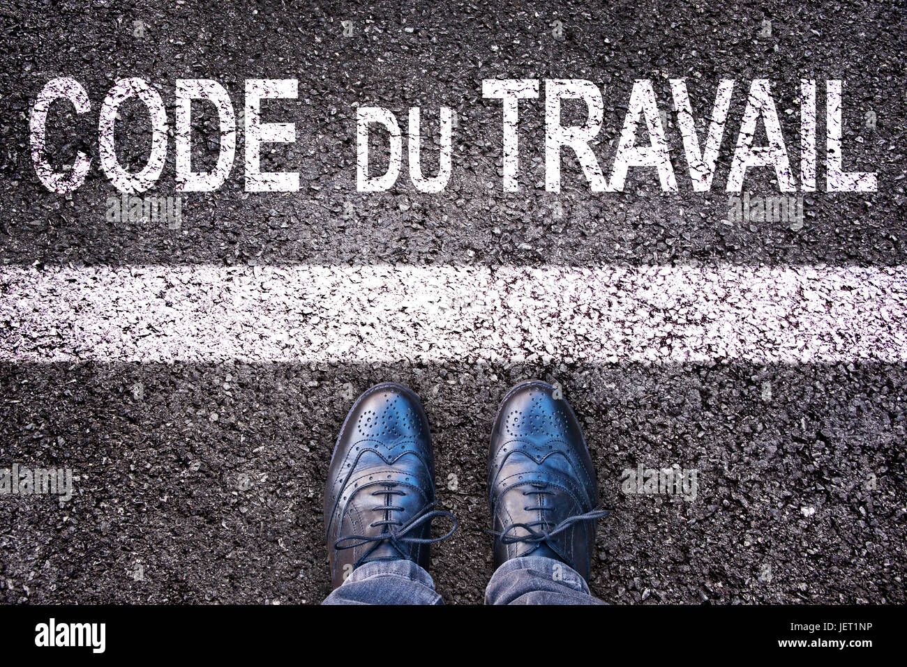 Code du travail (meaning labor code in French) written on an asphalt road background with legs - Stock Image