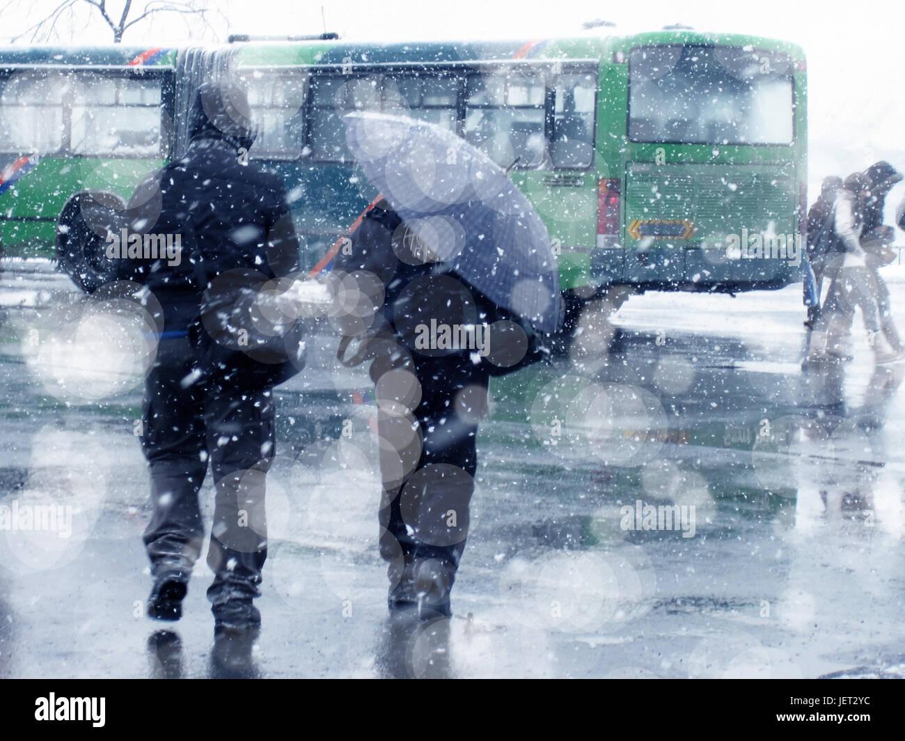 people walking on city street under snowing - Stock Image