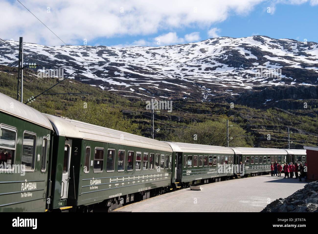 Flam Railway train in the station with passengers on platform. Vatnahelsen, Aurland, Norway, Scandinavia, Europe - Stock Image