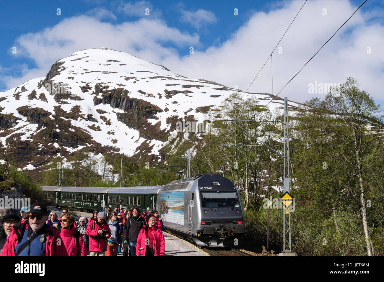 Flam Railway train in the station with G Adventures tourist group of passengers on platform. Vatnahelsen, Aurland, - Stock Image