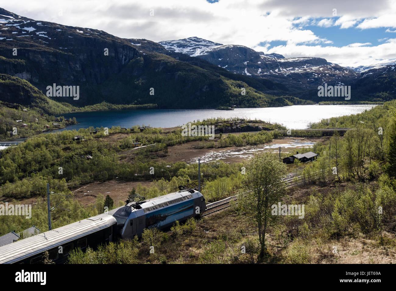 Flam Railway train journey through lake and mountain landscape in summer. Vatnahelsen, Aurland, Norway, Scandinavia, - Stock Image