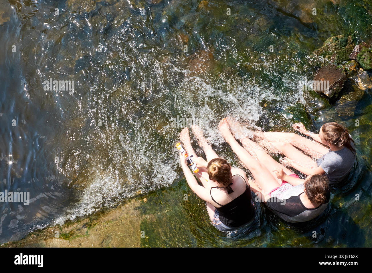 Three girls sit in a pool by a weir on the river Thames during a heat wave in summer. - Stock Image