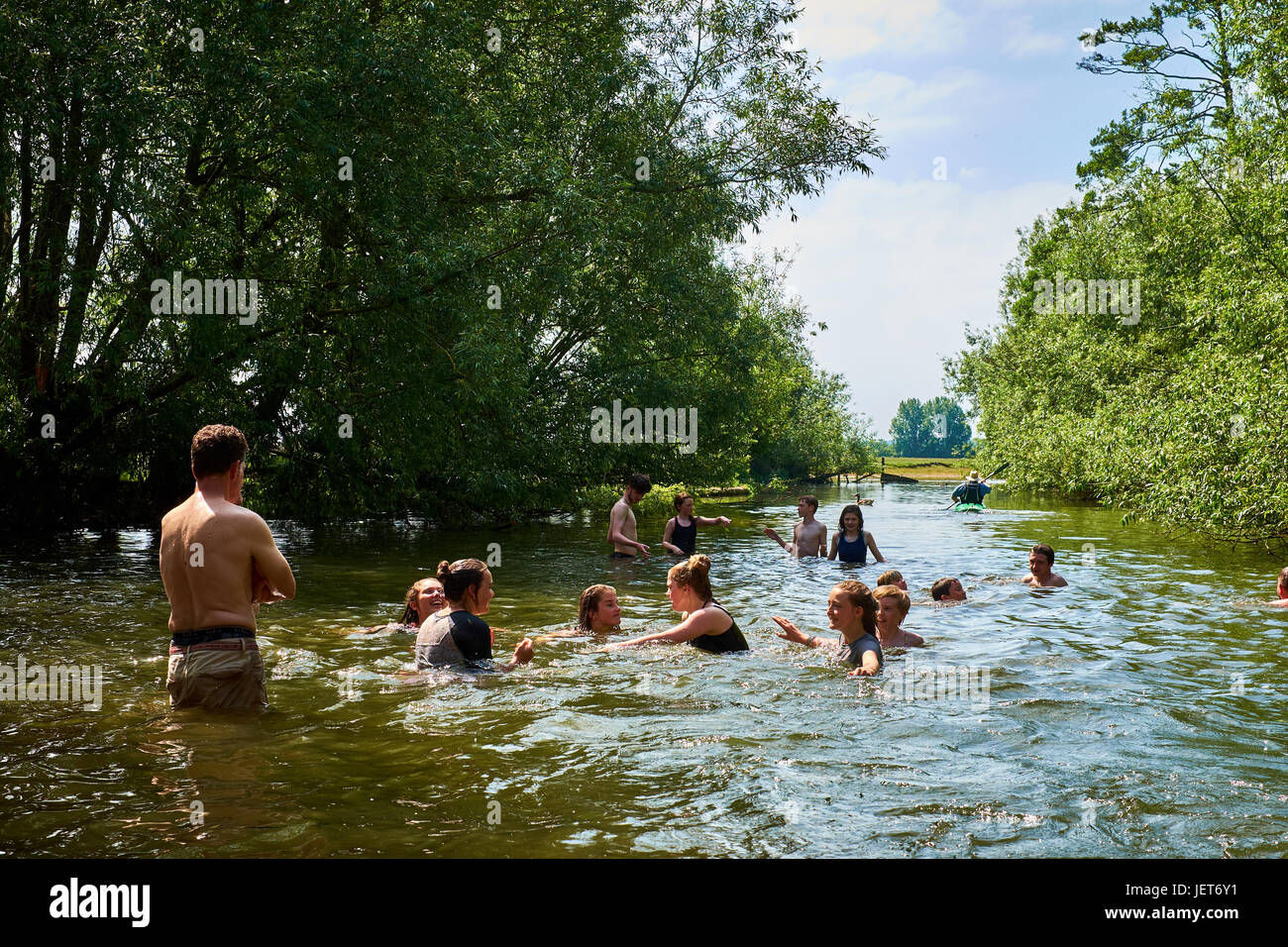 Adults and children play in the river Thames near Oxford on a hot summer day. - Stock Image