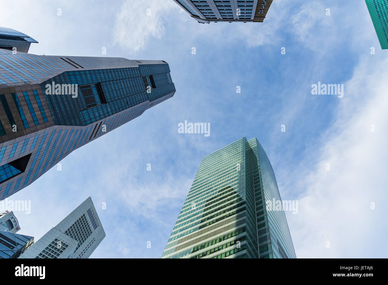 Singapore - June 17, 2017: Bottom view of modern skyscrapers in business district area against blue sky, Skyscraper - Stock Image
