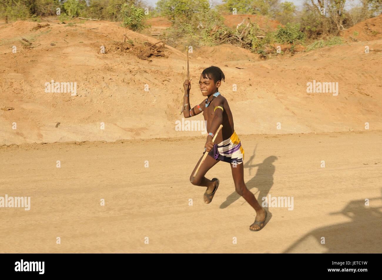 Boy, tribe Ari, spear, street, run, southern Omotal, south Ethiopia, - Stock Image