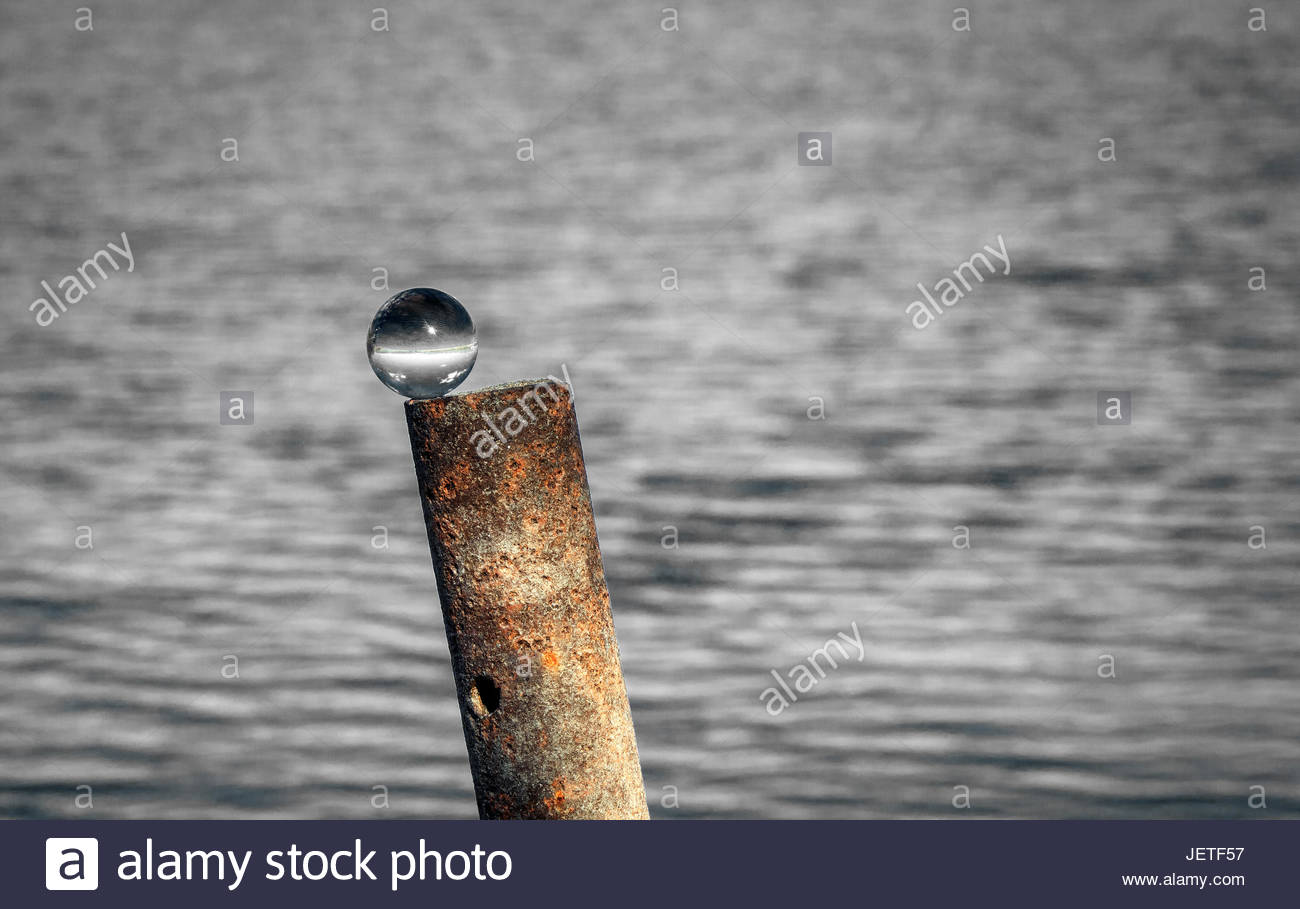 Selective Color Glass Ball Set Atop A Rusty Metal Pipe Sticking Up Out Of The Water Near Shore At Lake