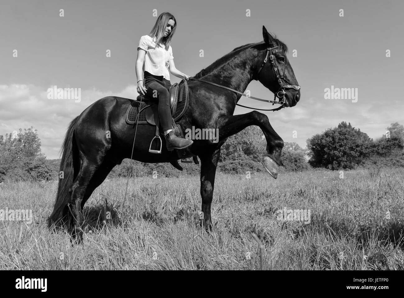young riding girl and her black stallion in nature - Stock Image