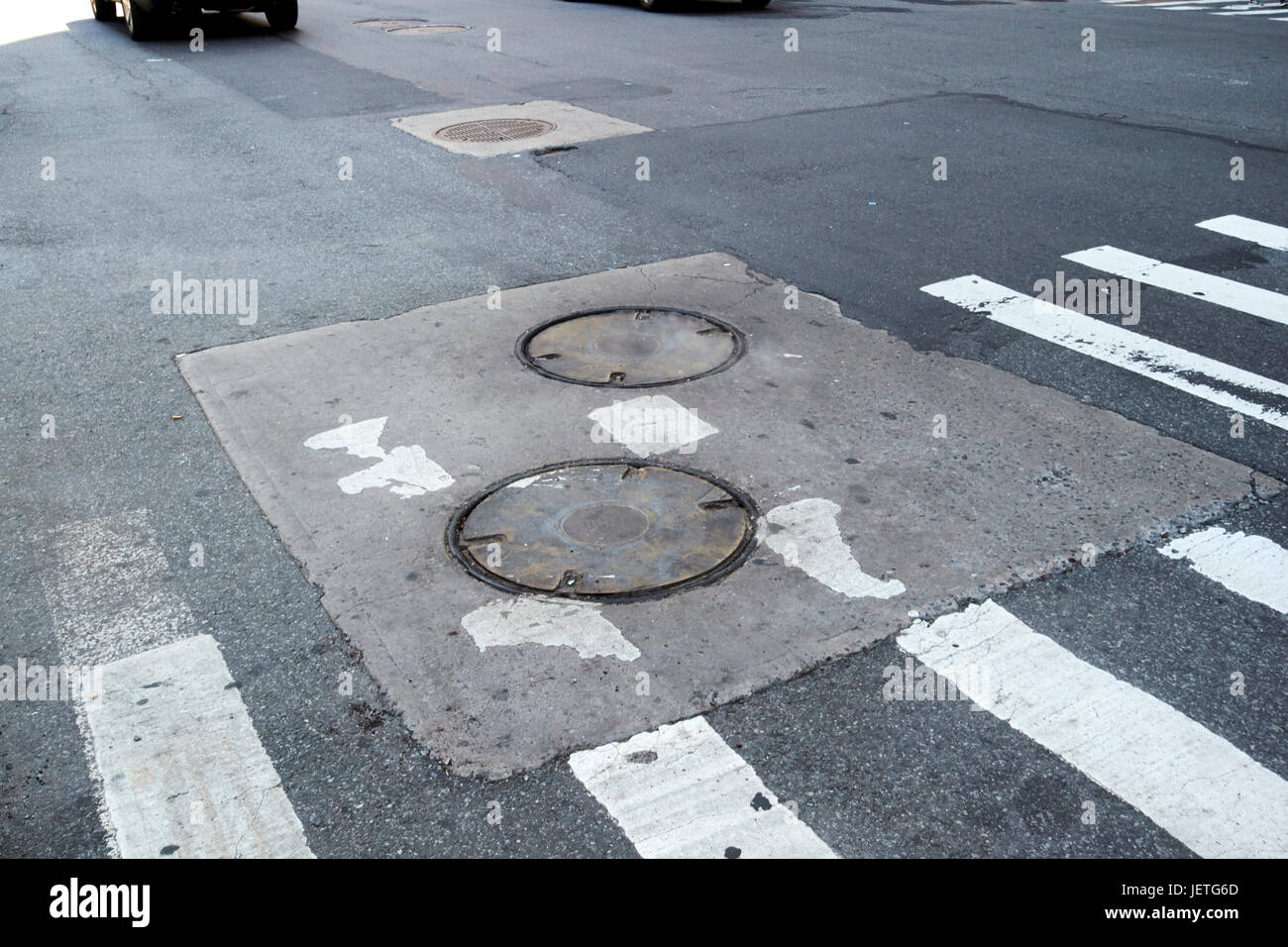 steam rising from manhole covers in road in lower manhattanNew York City USA - Stock Image