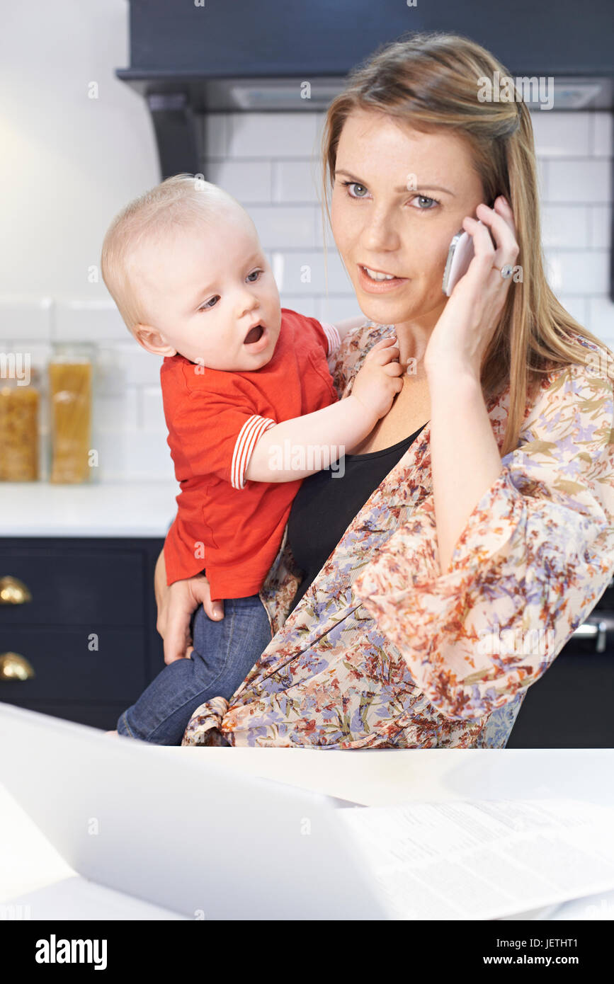 Busy Mother With Baby Coping With Stressful Day At Home - Stock Image