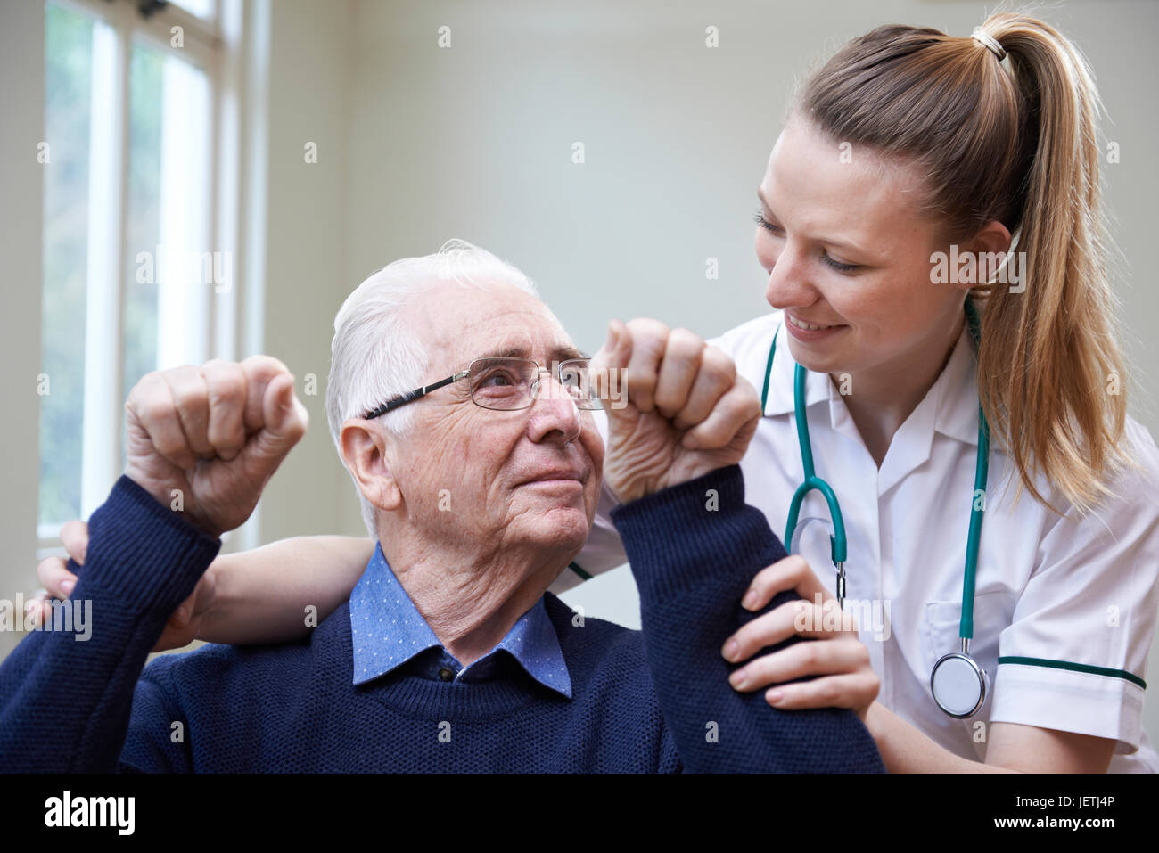 Nurse Assessing Stroke Victim By Raising Arms - Stock Image