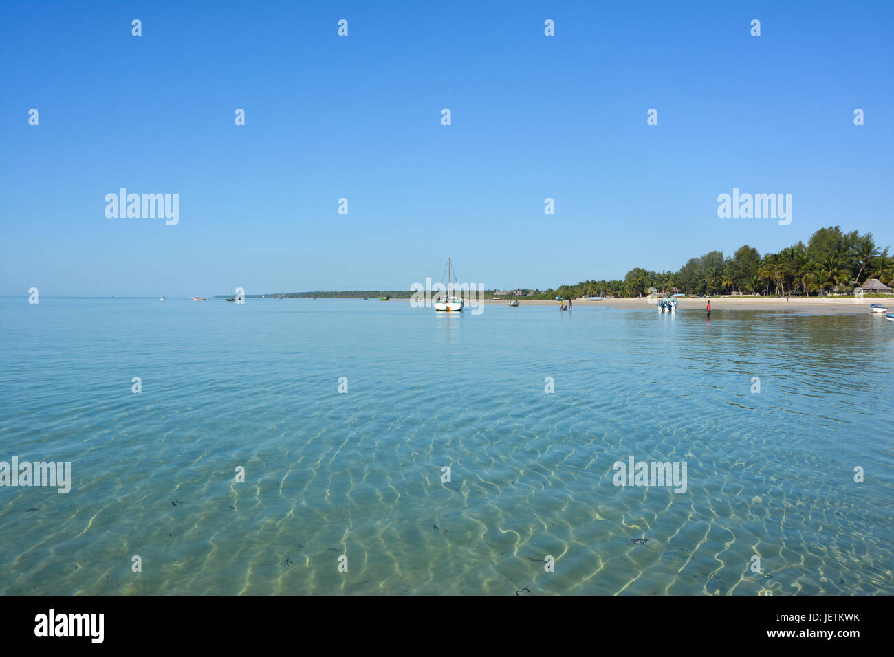 Flat ocean scene with boats by an island off Mozambique Stock Photo