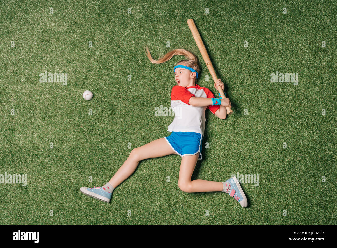 top view of little girl pretending playing baseball on grass, athletics children concept - Stock Image