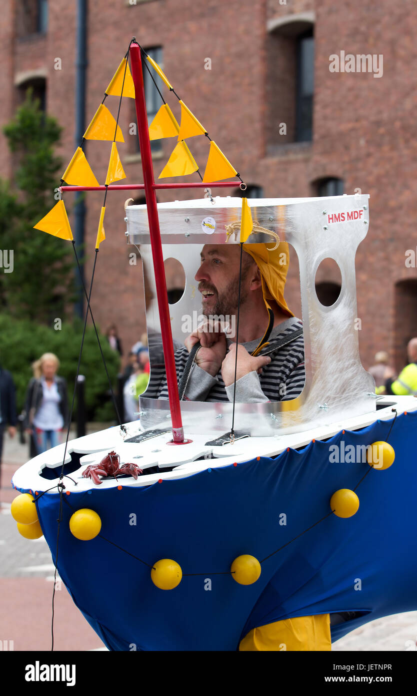 Men dressed as trawlermen in a toy boat and carrying a plastic shark to entertain the public at an outdoor event Stock Photo