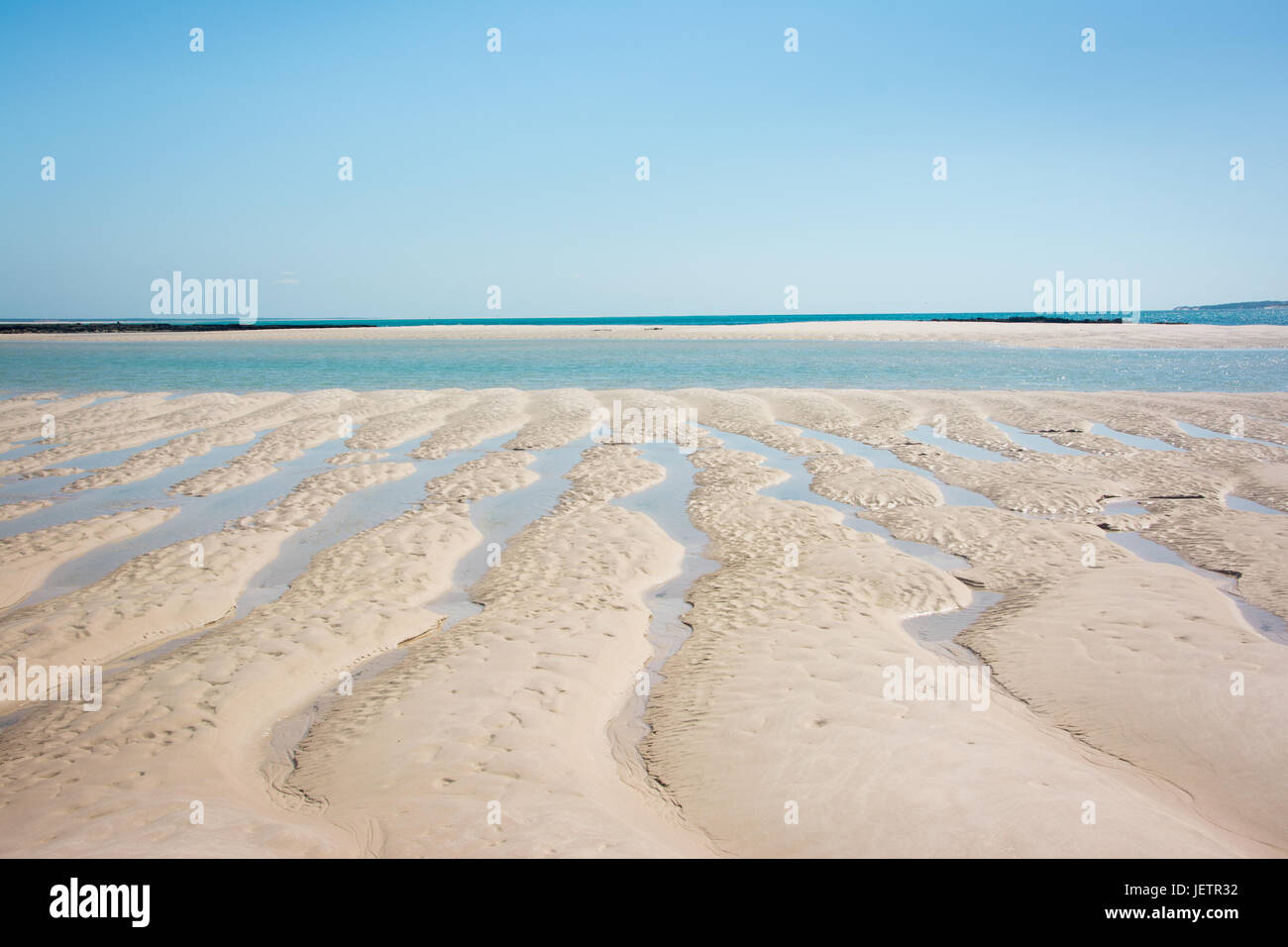 Patterns in the sand and bright blue sky, on a desert island off the coast of Mozambique - Stock Image