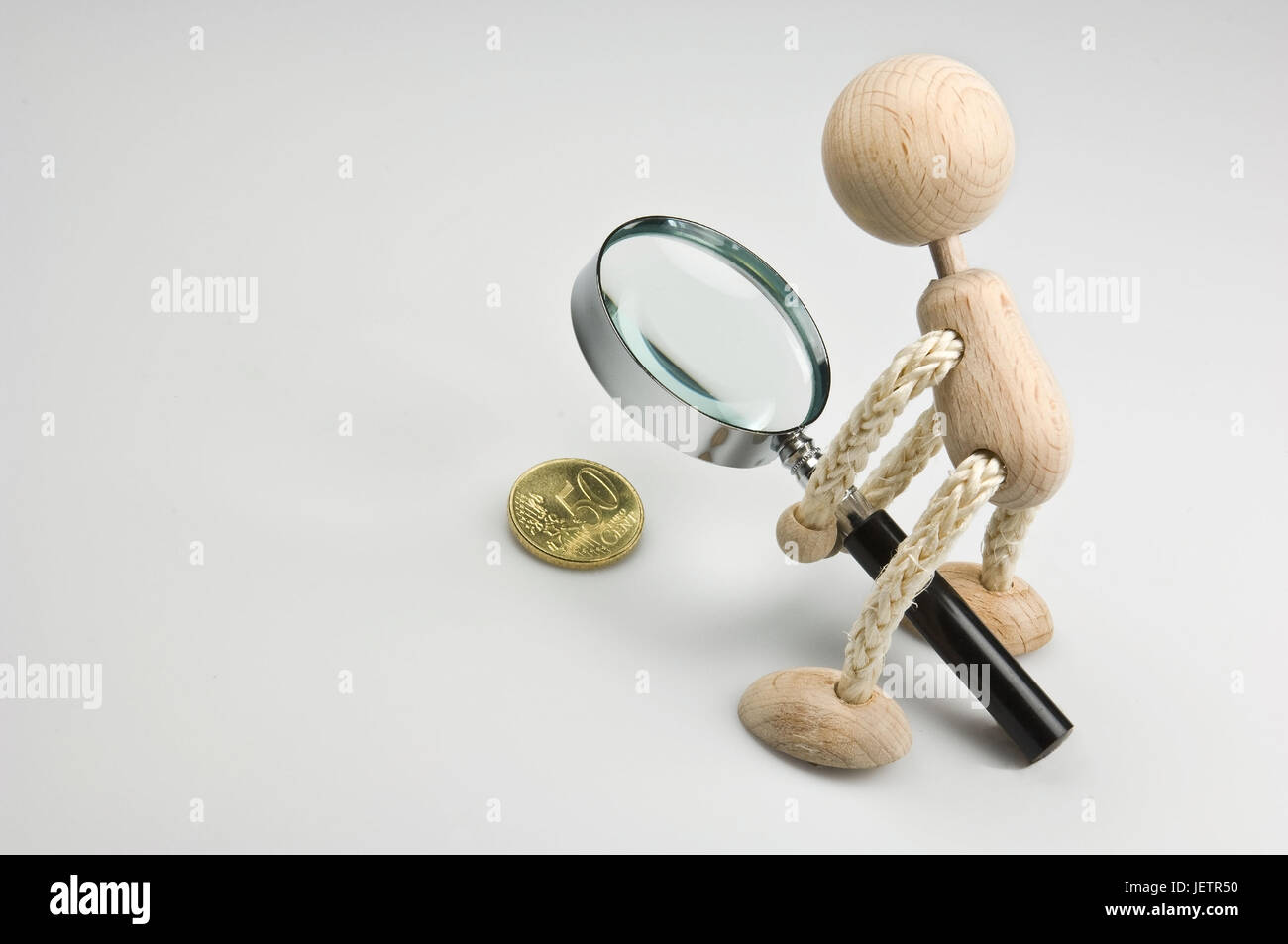 Wooden figure holds a magnifying glass about a 50 euro cent coin, Holzfigur haelt eine Lupe ueber ein 50-Eurocent - Stock Image