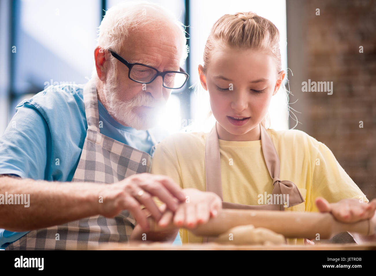 grandchild and grandfather cooking and making dough for cookies with kitchen utensils at kitchen table, cooking - Stock Image