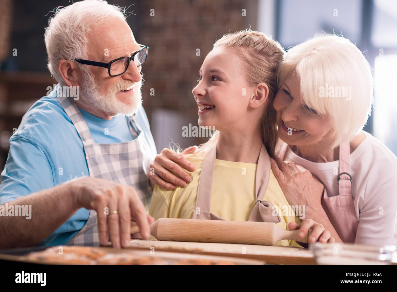 grandmother, grandfather and granddaughter cooking and kneading dough for cookies with kitchen utensils at kitchen - Stock Image