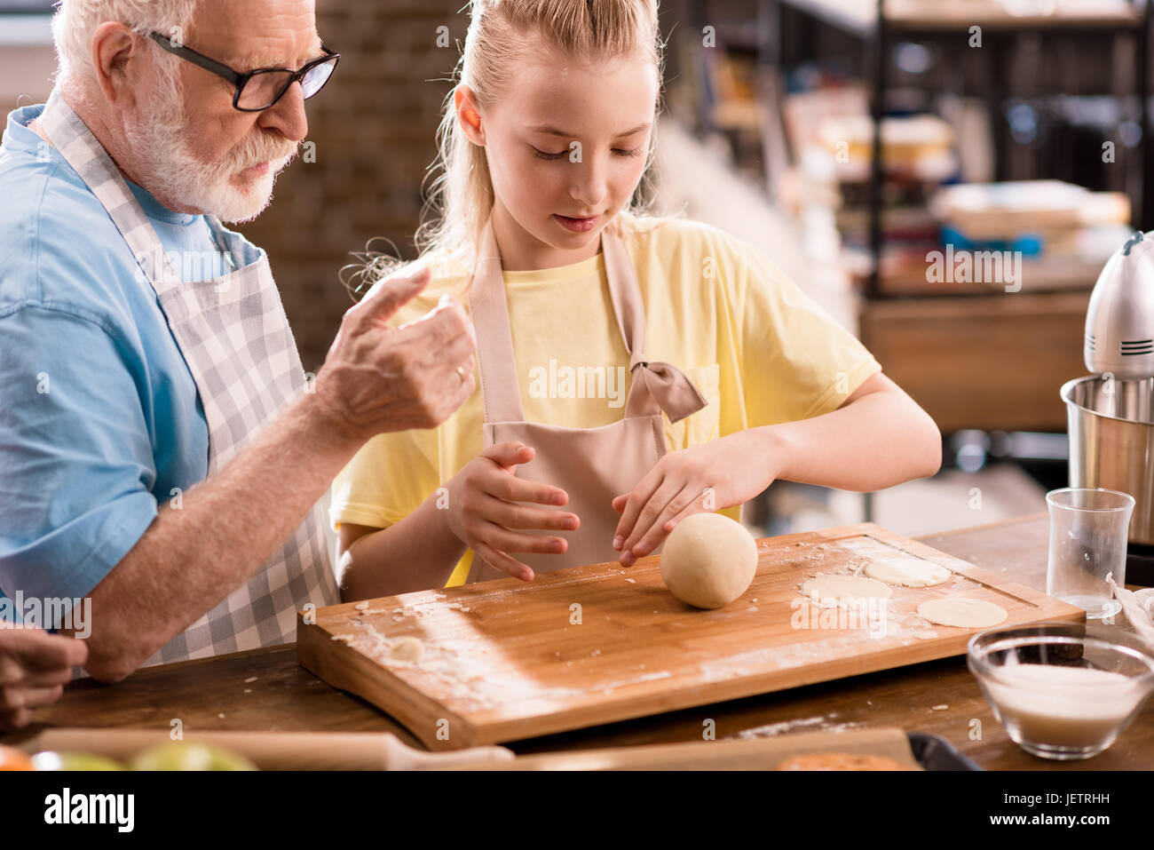 grandfather and granddaughter cooking and kneading dough for cookies at kitchen table, cooking in kitchen concept - Stock Image