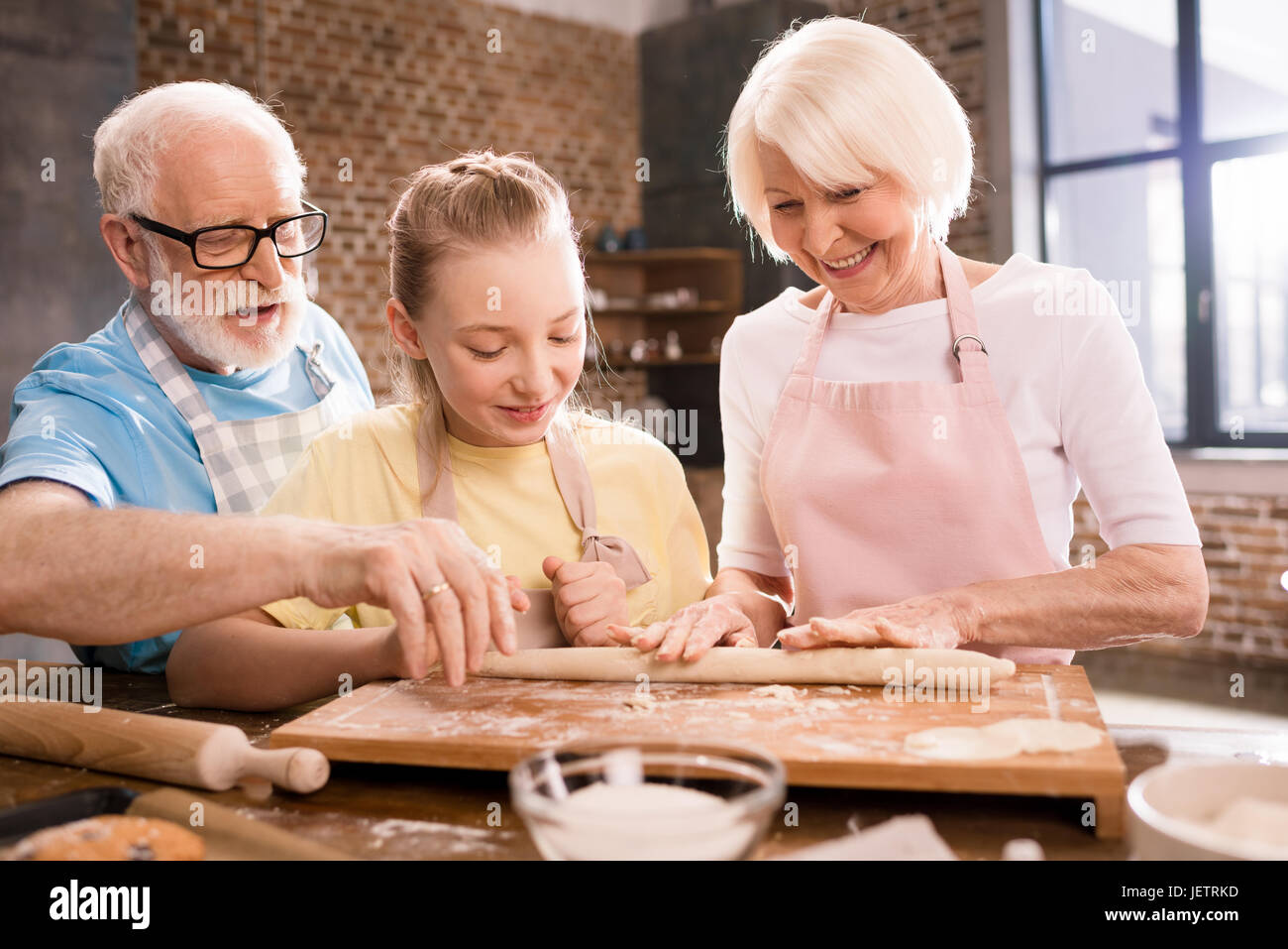 grandmother, grandfather and granddaughter cooking and kneading dough for cookies at kitchen table, cooking in kitchen - Stock Image