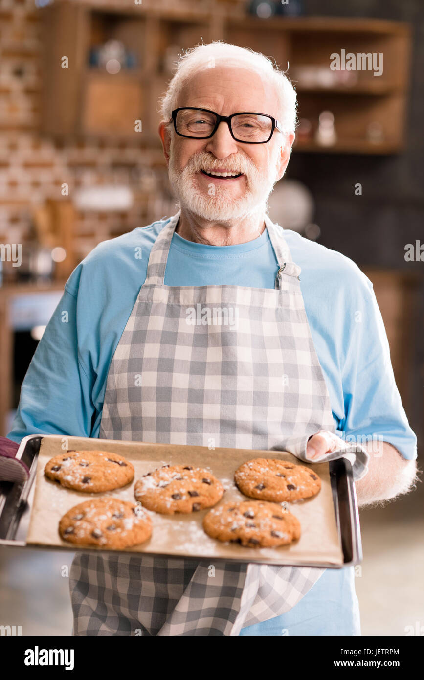 Senior man in apron holding tray of delicious cookies, cooking in kitchen concept - Stock Image