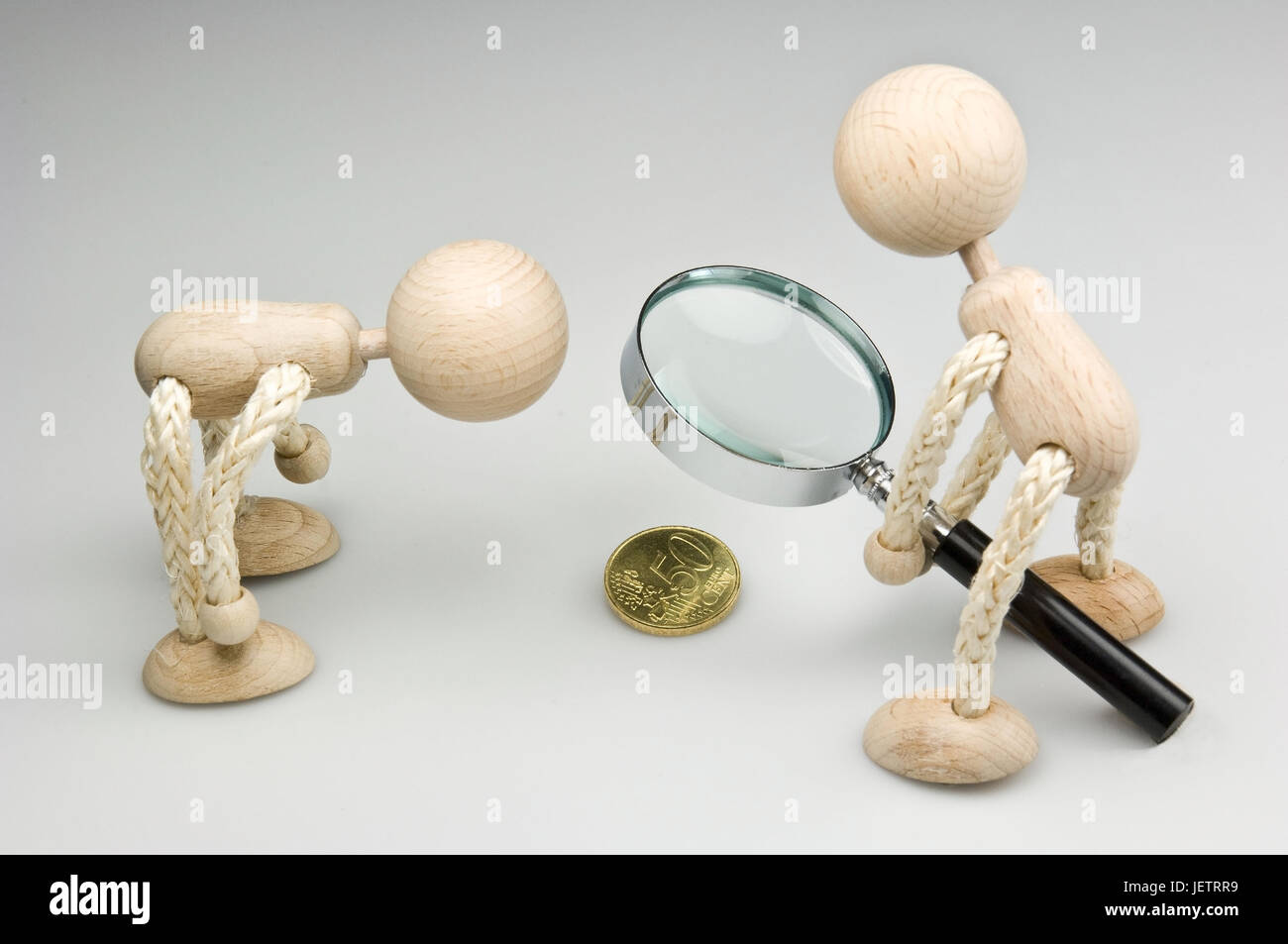 Two wooden figures with magnifying glass and 50 euro cent coin, Zwei Holzfiguren mit Lupe und 50-Eurocent-Muenze - Stock Image