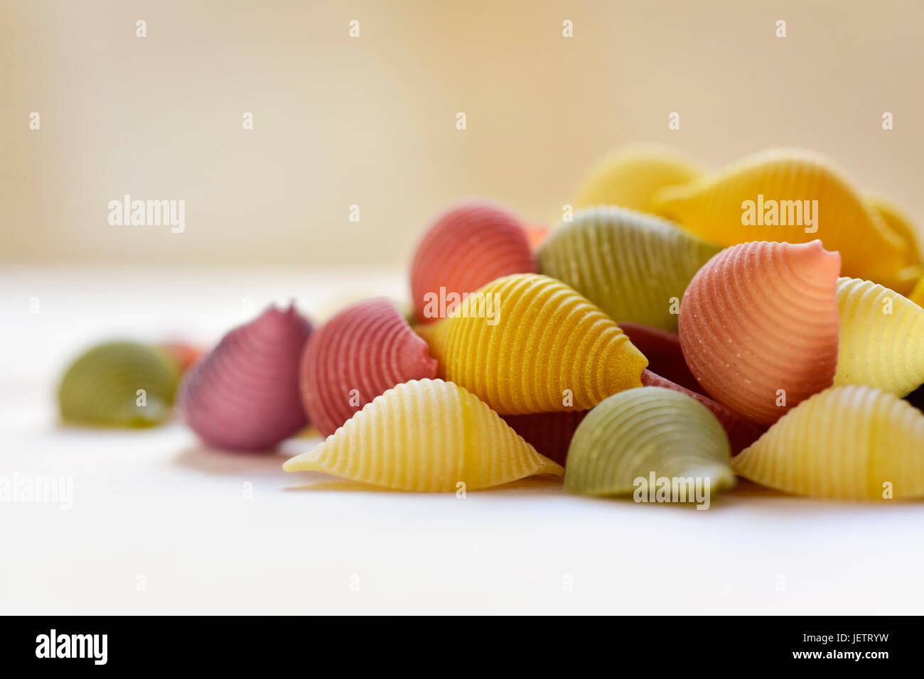 closeup of a pile of uncooked conchiglie, italian seashell pasta, with different colors: yellow as usual, red made Stock Photo