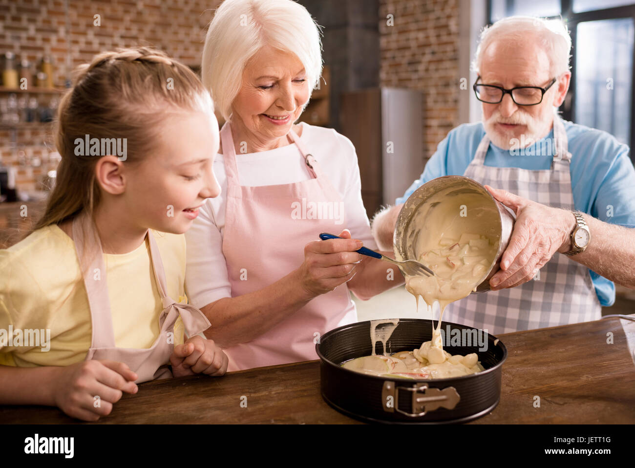 happy grandparents and girl cooking together at home - Stock Image