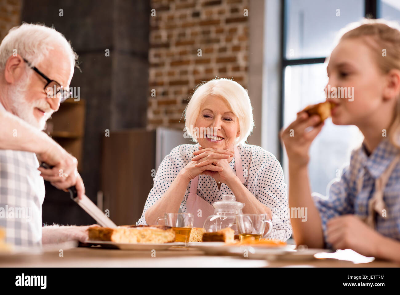 side view of man cutting homemade pie with family near by - Stock Image