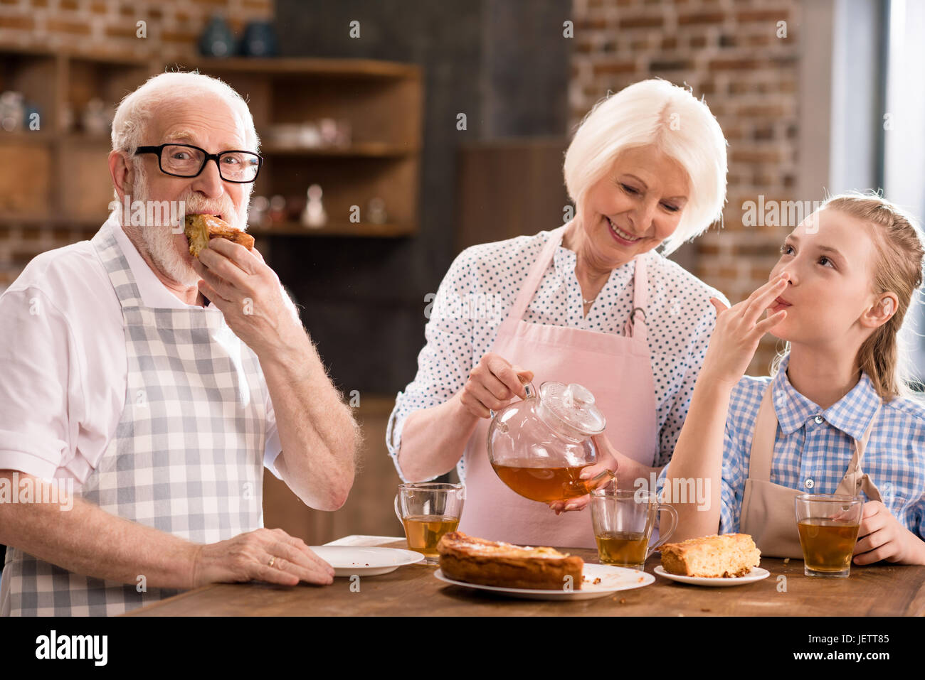 grandparents and girl drinking tea with pie together at home - Stock Image
