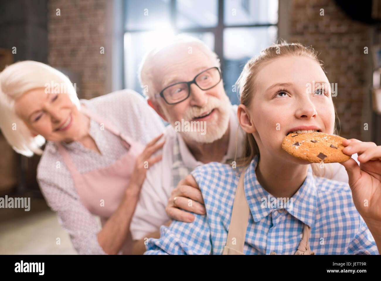 girl eating homemade cookie with grandparents behind - Stock Image
