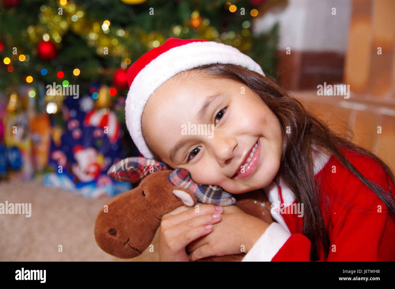 Beautiful Smiling Litle Girl Wearing A Christmas Clothes Hugging Moose Teddy With Tree Background Some Presents