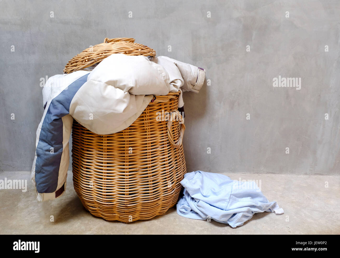 Overflowing wicker laundry basket. Household chore concept. - Stock Image